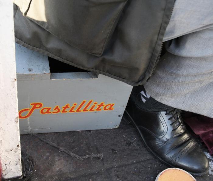 """EL Pastillita"" is written on the box on which he is sitting"